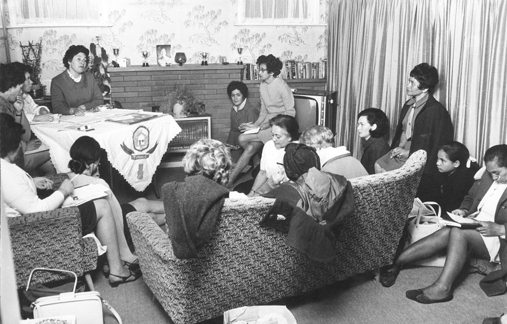 Māori Women's Welfare League members meet in a living room. The executive table is covered with a cloth embroidered with their logo. Tūmanako, 9 November 1970.  [Māori Women's Welfare League](/files/schools/hm62-maori-womens-welfare-league-english.mp3)