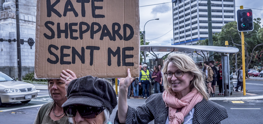 Women in 2017 Women's March in Wellington holding a sign saying 'Kate Sheppard sent me'