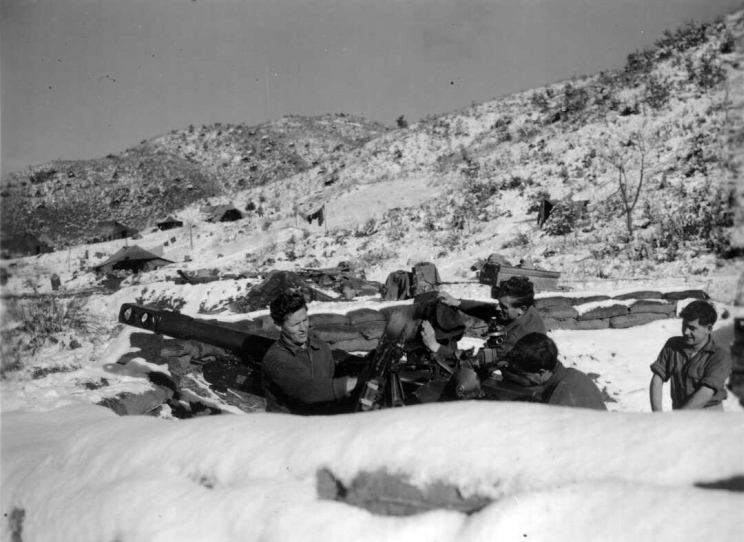 Four men seen cleaning a large gun shortly after a heavy snow fall.