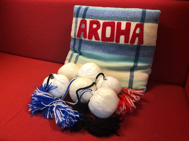Cushion with the word Aroha on it and 6 poi.
