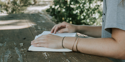 Young person's hands holding open book on a table outside