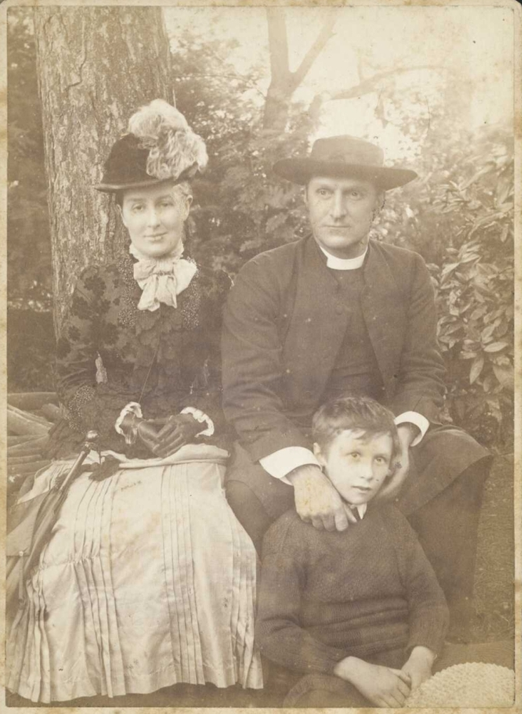 Portrait of a young family, a young boy is seated on the ground in front of his father.