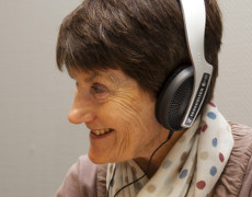 A woman wearing headphones, taking part in oral history training.