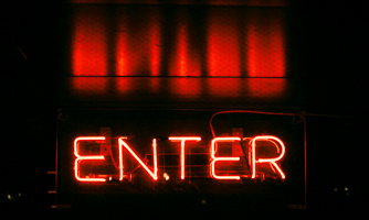 Word 'ENTER' in lights in front of a stage with red curtains