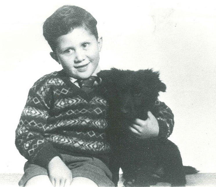 A studio photo of a small boy wearing a tie and jersey hugging a dog.