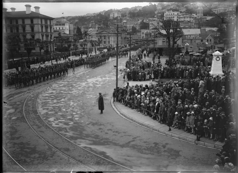 Looking south along Lambton Quay as the parade marches down the street which has been cleared. Crowds line the footpaths.