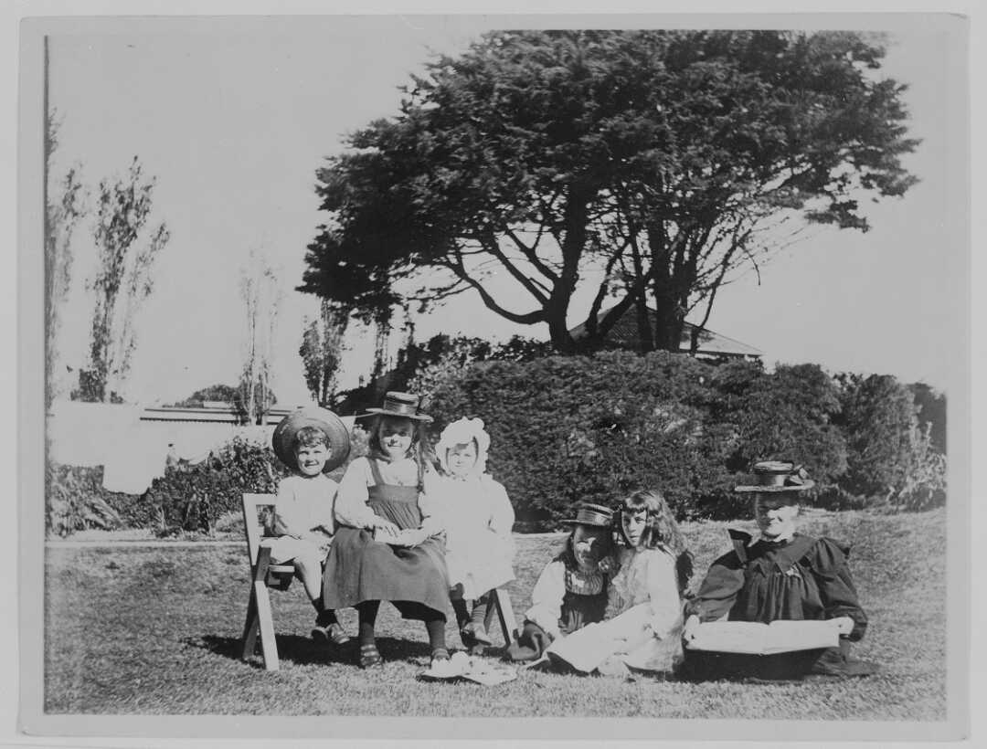 Beauchamp family children seated outside on the lawn in formal dress