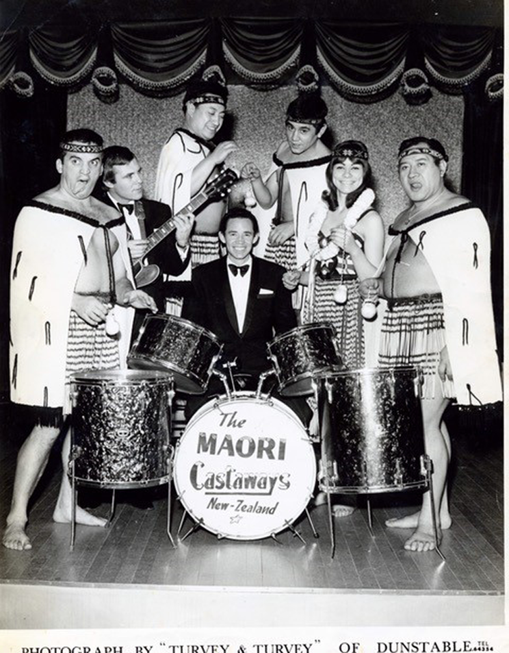 A gorup of Māori performers standing around a drumkit.