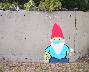 Colourful gnome painted on concrete wall.