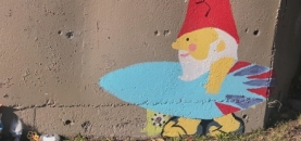 Gnome painted on concrete wall holding a surfboard and a gathering on the grass in front of the wall of small figurines appearing to have a picnic.