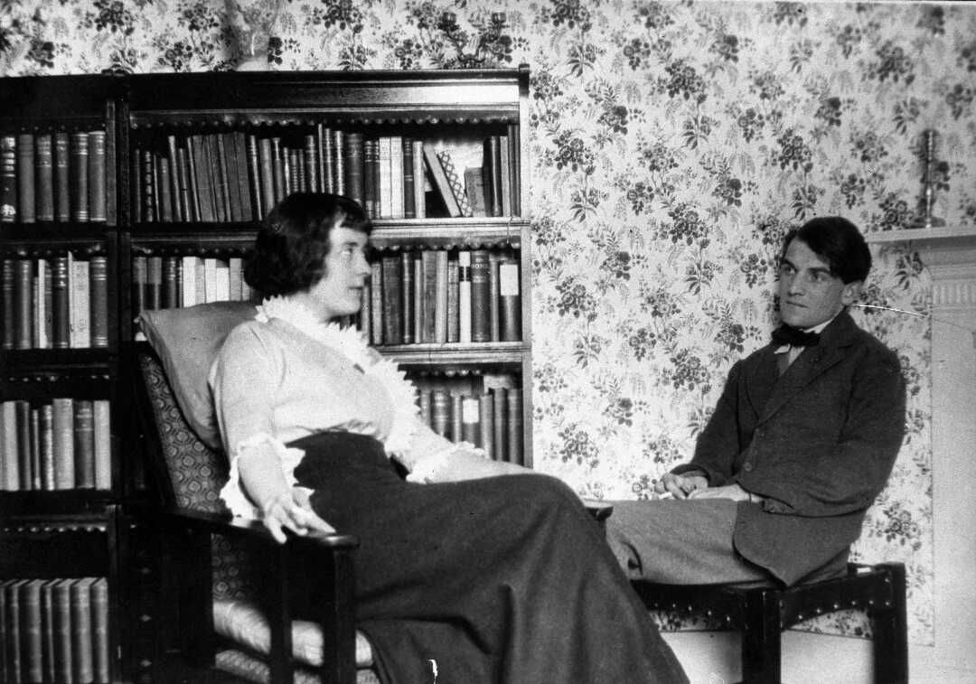 Katherine Mansfield and John Middleton Murry sitting inside their flat in the study with rows of books behind them.
