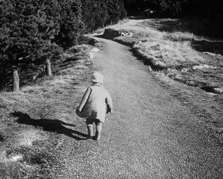 Child walking up a gravel road.
