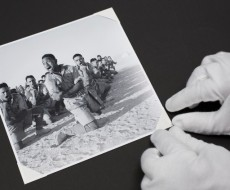Handling a photographic print with white gloves.
