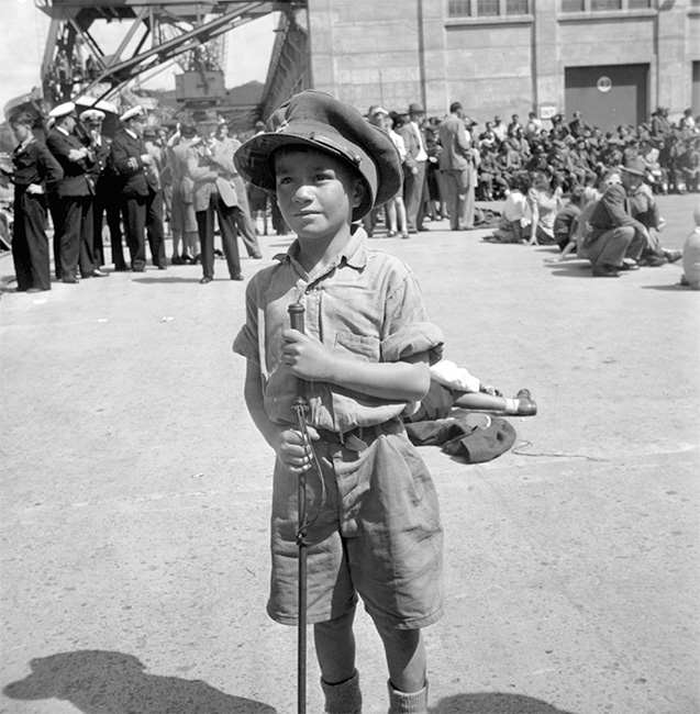 The return of the 28th Māori Battalion, January 1946. A young Māori boy, wearing school uniform and a soldier's cap, waits on the wharf in Wellington.  [Māori Battalion](/files/schools/hm16-maori-battalion-english.mp3)
