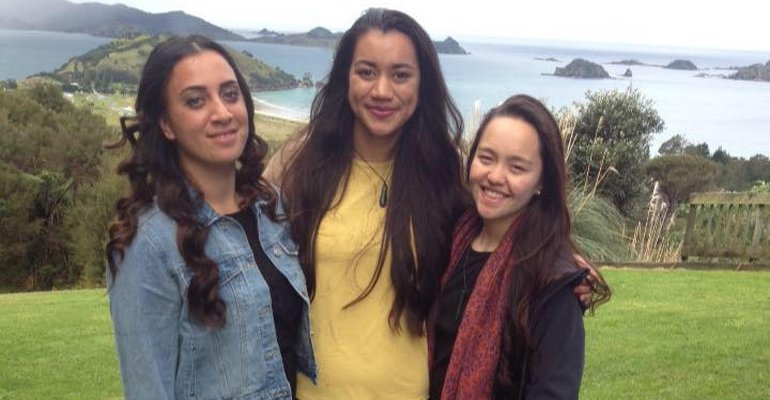 Three kura kaupapa students with Matauri Bay in the background.