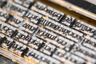 The metal type set and ready to print for 'In the mirror, and dancing'.