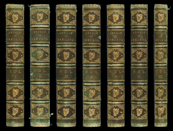 Spines of the seven volumes of Annals of Ireland, illustrated with Celtic harps.