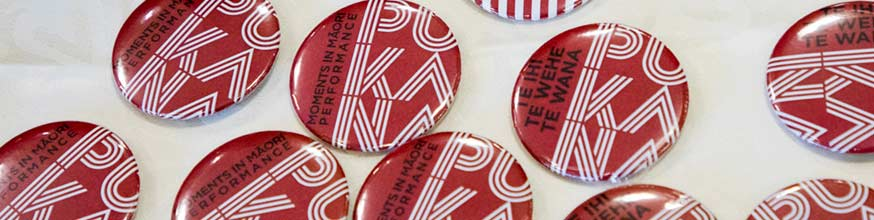 Badge red and white with work Pūkana on it.