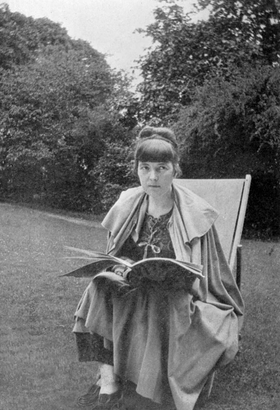 Katherine Mansfield sitting in a chair outdoors with a magazine or book in her lap