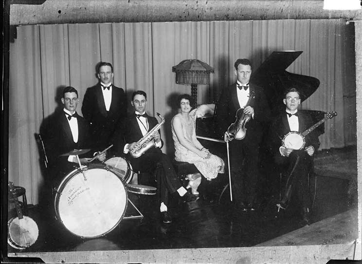Black and white photo of 5 men and one woman in formal dress sitting with their instruments, which include a piano, drum and banjo.