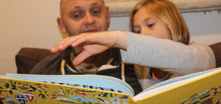 Father and daughter reading at home.