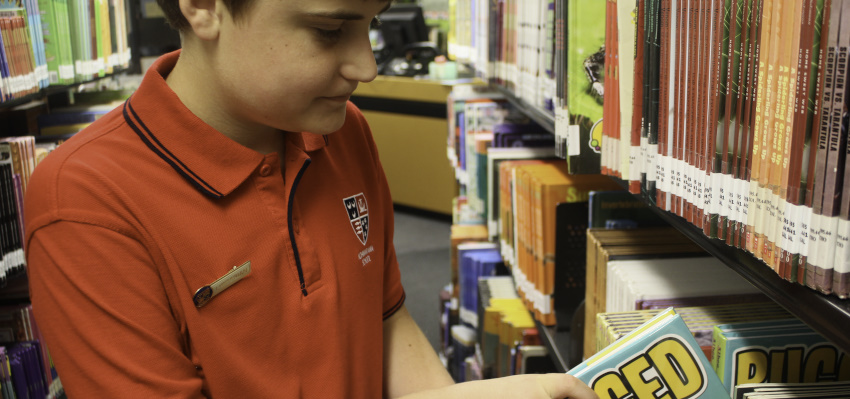 School student looking at a shelf of Services to Schools books.