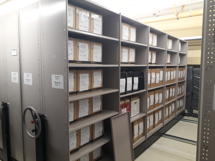 Shows the Norton collection stored on shelves in archival boxes with white labels.