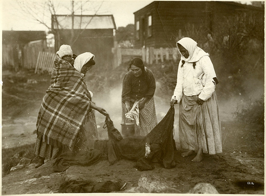 Three Māori women, wearing warm clothing, cook food in a natural steam vent. One woman has a baby on her back wrapped in a woollen blanket.  [Cooking with steam](/files/schools/hm82-cooking-with-steam-english.mp3)