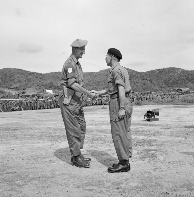 Two men in military uniform shake hands during a ribbon pinning ceremony.