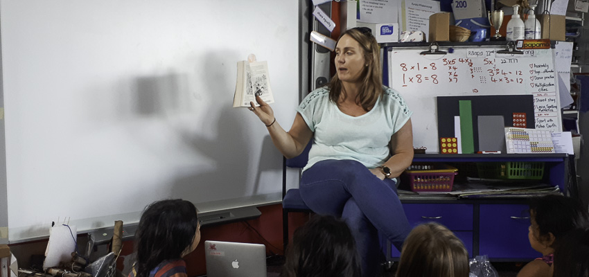 School teacher reading aloud to school students