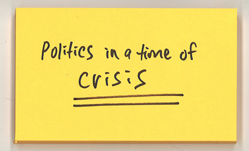 "Post-it note with words ""Politics in a time of crisis"" written on it."