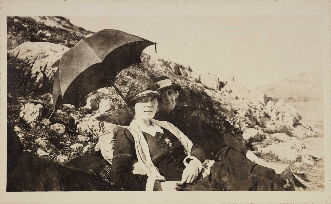 Katherine Mansfield reclining beside rocks with a friend, both under an umbrella to keep out of the sun.