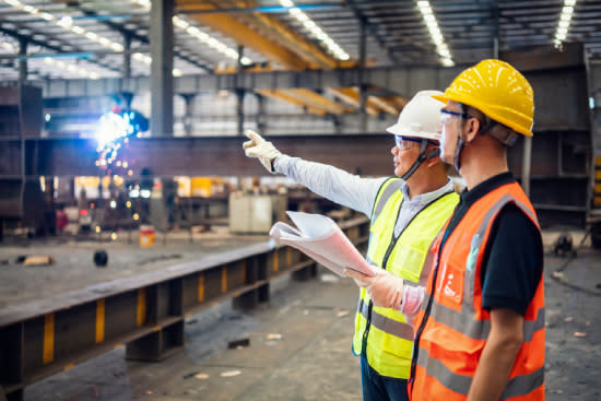 Two men pointing at industrial machinery in factory