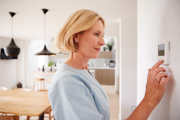 Woman adjusting heating in home