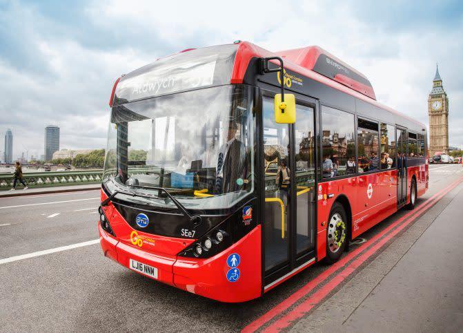 A London bus driving over a bridge.