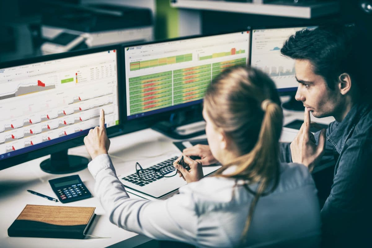 People examining data on computer monitor