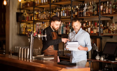 Staff looking at tablet behind a bar