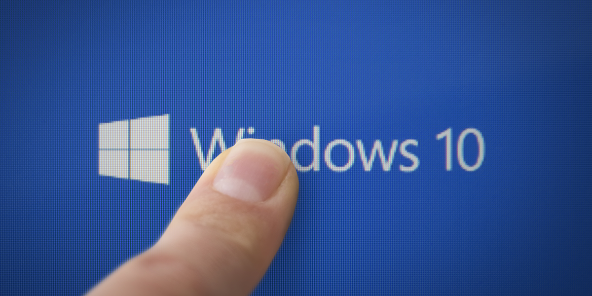 A person pressing their finger on to a Windows 10 logo.