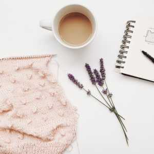 Piece of knitting with cup of coffee, sprig of lavender, and a notebook