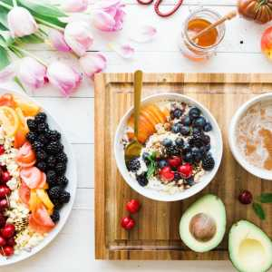 Dishes with healthy fruits, cereal, avocados, a jar of honey, and a bunch of tulips