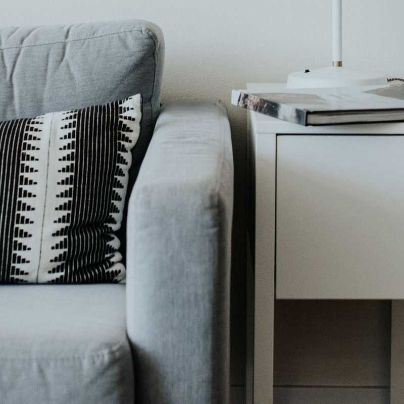 Gray couch with black and white striped pillow and a white end table with lamp