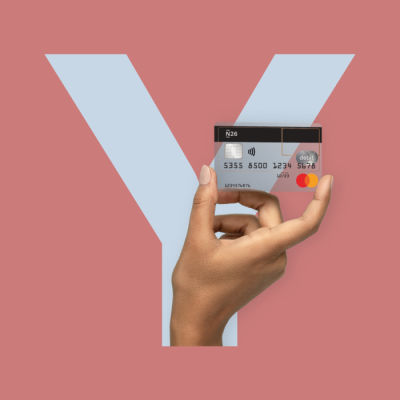 Hand holding an N26 card with the letter Y in the background.