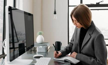 Freelance woman writing in front of a computer.