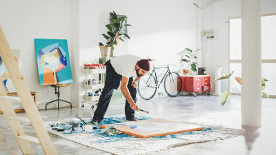 a freelance artist painting on the floor with blue color on an orange canvas in a bright white room.