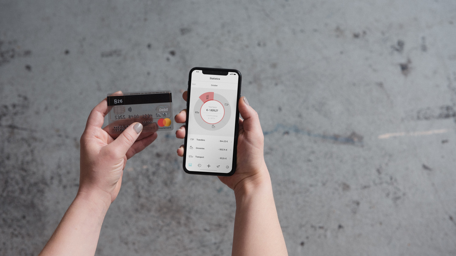 N26 Press Image showing a person sitting while holding the N26 Debitcard Mastercard and her phone