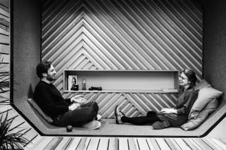 Two people sitting and talking in the wooden lounge area.