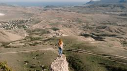 Woman standing on top of a small mountain.