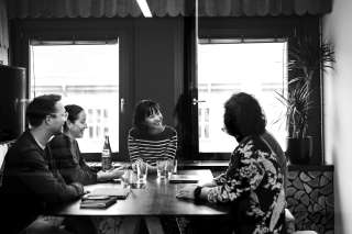 Black-and-white picture of people talking around a table