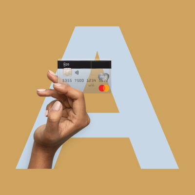 Hand holding an N26 card with the letter A in the background.