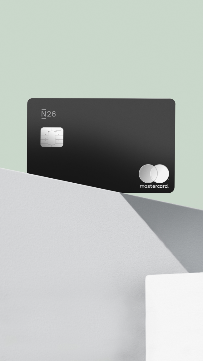Black N26 Metal card on top a gray concrete block.
